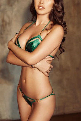 Slim high class girl in green bikini with curly brown hair