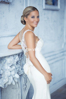 Posh blonde escort in a white wedding dress standing next to a fireplace