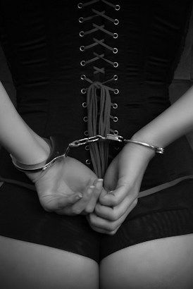 Submissive woman with her hands cuffed and wearing a basque
