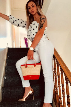 Leggy blonde in white jeans halfway up the stairs
