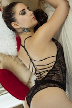 Brunette lying on a bed in sexy lingerie